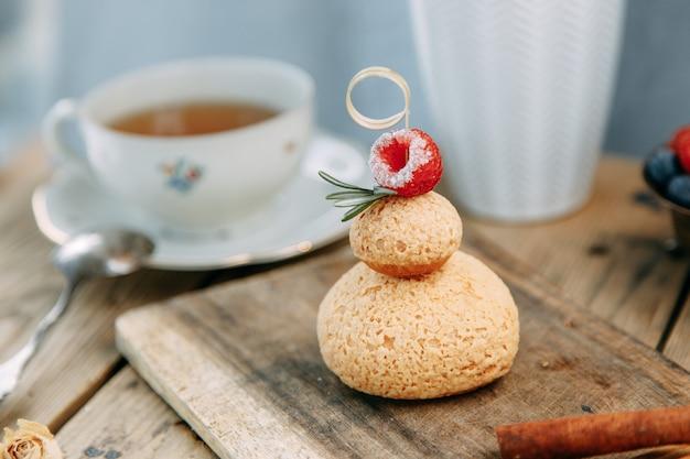 Vanillepuddingkuchen mit schokoladen- und beerenfüllung. runder kuchen mit mousse-creme auf einem holztisch.