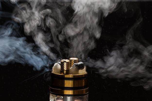 Vape nahaufnahme mit rauche auf einem schwarzen hintergrund