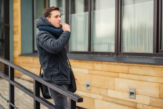 Vaping. junge männer, die eine elektronische zigarette vaping sind. vaping im freien.