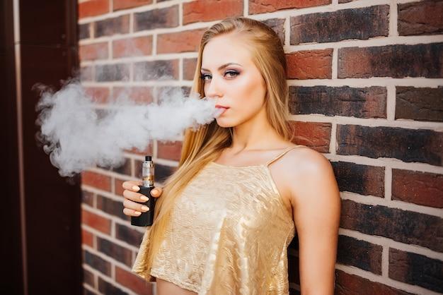 Vaping. junge schönheit, die draußen e-zigarette mit rauche raucht. dampf-konzept.