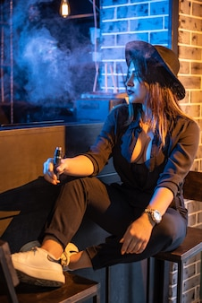 Vaping. junges schönes mädchen, das elektronische zigarette im verein raucht.