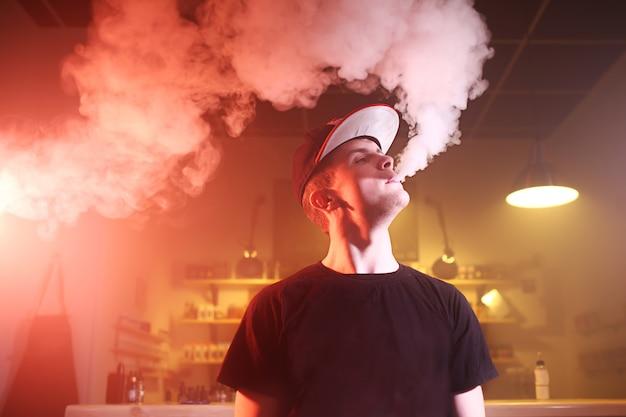 Vaping man in einer wolke von dampf in einem vape bar