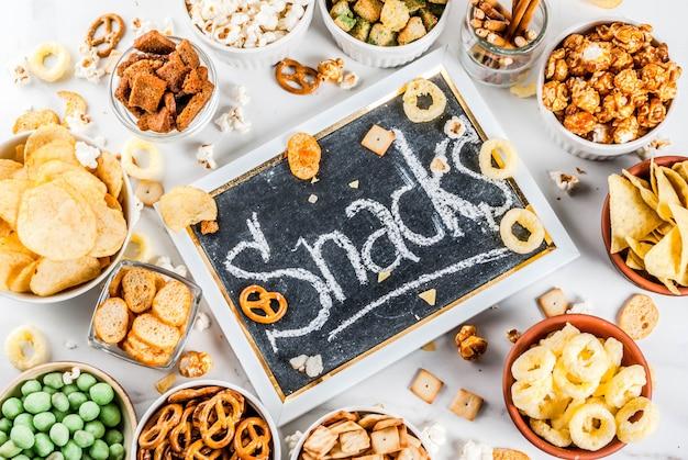 Variation verschiedene ungesunde snacks cracker, süß gesalzenes popcorn, tortillas, nüsse, strohhalme, bretsels