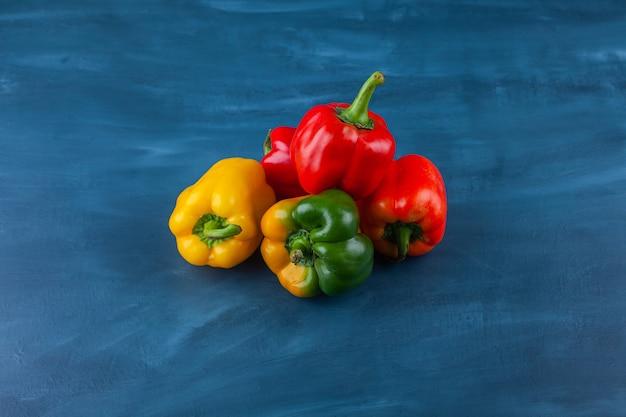 Variation verschiedenfarbiger paprika auf blauer oberfläche. Kostenlose Fotos