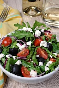 Variation von griechischem salat mit rucola-kirschscheiben feta und oliven