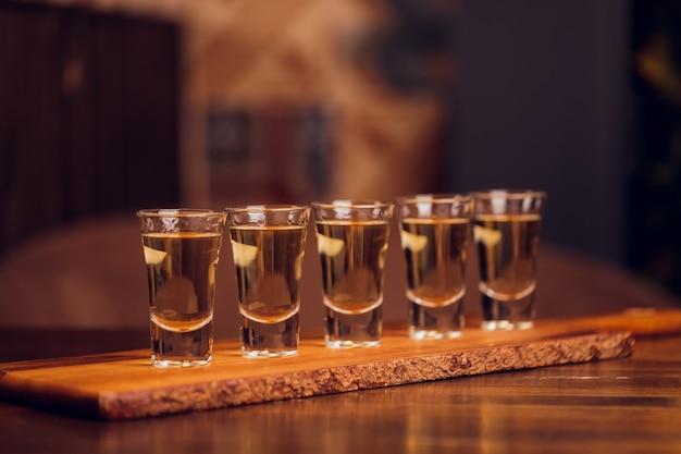 Variation von harten alkoholischen schüssen, die auf der bartheke serviert werden. unscharfe flaschen auf hintergrund.