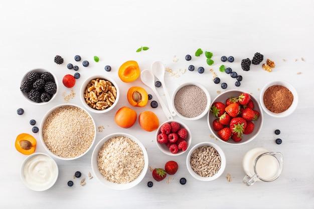 Variation von rohem getreide, obst und nüssen zum frühstück. haferflocken und stahl geschnitten, gerste, walnuss, chia, aprikose, erdbeere. gesunde zutaten