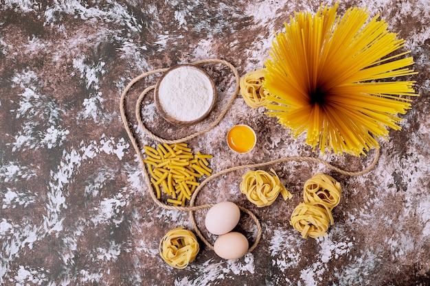 Variation von rohen nudeln mit eiern und mehl auf holztisch.