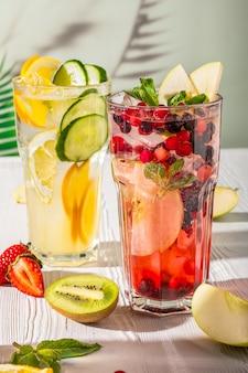 Variationen von limonaden mit verschiedenen früchten und sirupen auf holztisch unter morgensonne