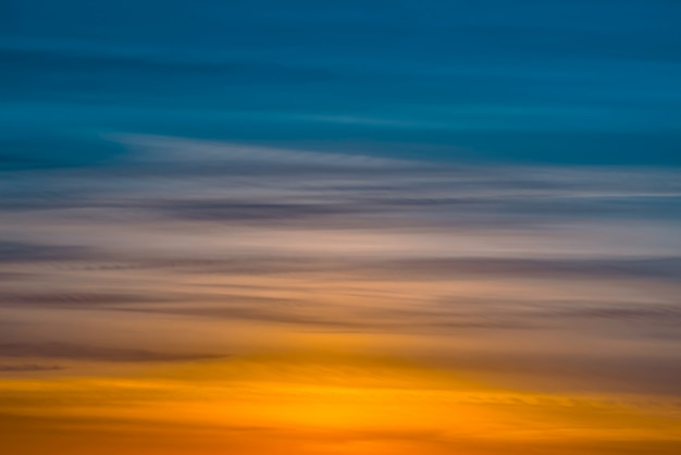Varicolored gestreifter dämmerungshimmel mit schatten der farben blau, cyan, kobalt, rosa, purpur, magenta. horizontale linien von malerischen wolken. atmosphärischer hintergrund des warmen himmels