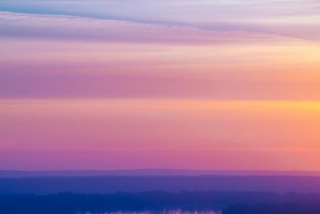 Varicolored gestreifter surrealer himmel mit schatten der blauen, cyan-blauen, rosafarbenen, purpurroten, magentaroten farben mit kobaltland und see. horizontale linien von glatten wolken. atmosphärisches bild des zarten himmels, des landes und des flusses.
