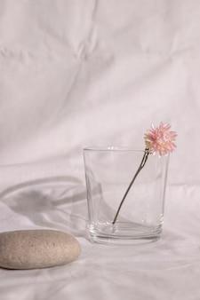 Vase der rosa trockenen blume auf tisch mit weißem stoff
