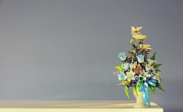 Vase des blumenstraußes der künstlichen blumen auf elfenbeintabelle mit grauer wand. gefiltertes weinlesetonbild