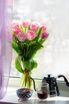 Vase mit blumen auf der fensterbank. tasse kaffee am fenster mit einem blumenstrauß. rosa tulpen in einer vase mit einer teekanne.