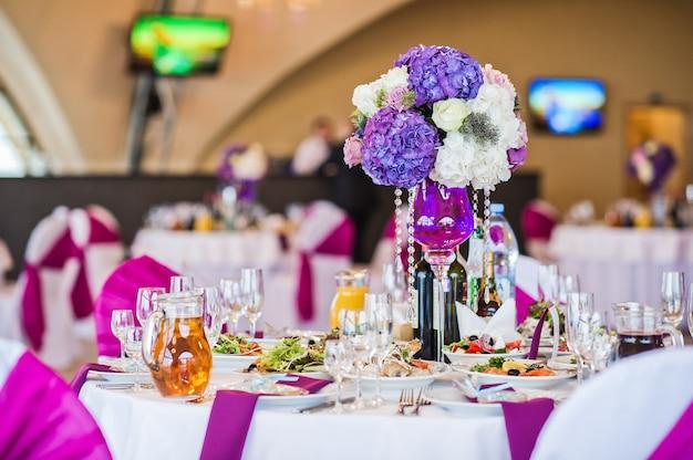 Vase mit blumen auf einem runden tisch serviert, abendessen in einem luxuriösen restaurant