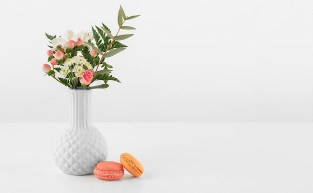Vase mit blumen und macarons daneben