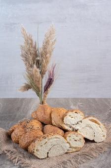 Vase mit dekorativen weizenstielen neben einem bündel mit sesam beschichteten, geschnittenen brotlaiben auf marmorhintergrund. foto in hoher qualität
