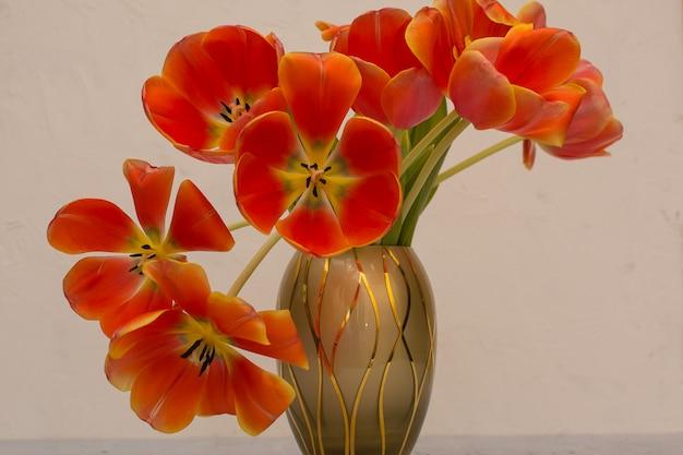 Vase mit einem strauß roter tulpen auf einem grau