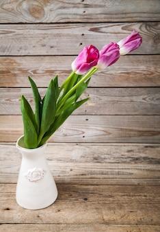 Vase mit natürlichen tulpen auf einem holztisch