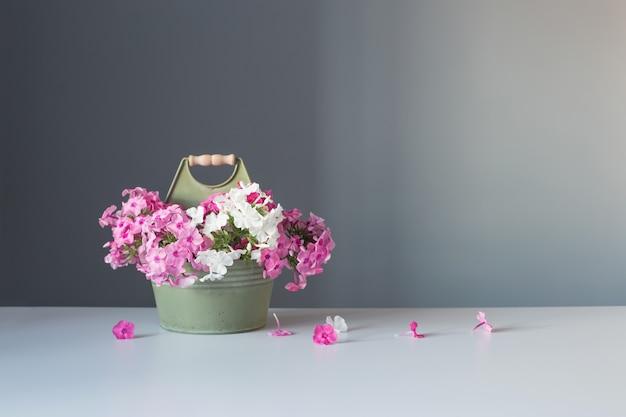 Vase mit rosa blumen auf grauem hintergrund