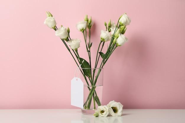 Vase mit rosen und leerem etikett gegen rosa hintergrund