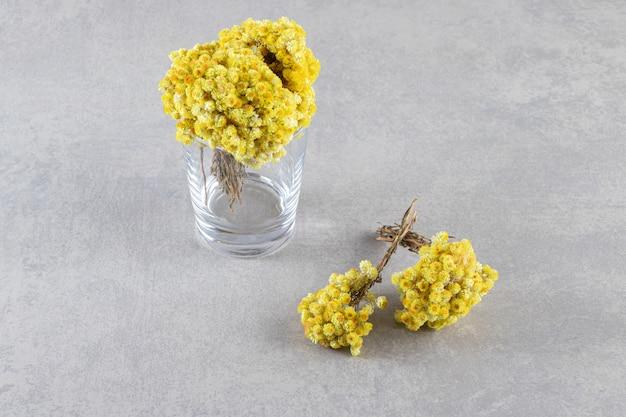 Vase mit schönen gelben blumen auf steinhintergrund gelegt.
