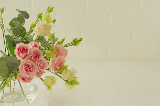 Vase mit schönen rosen, eustoma und eukalyptusblumen auf dem tisch, platz für text. zarte grußkarte für den urlaub.