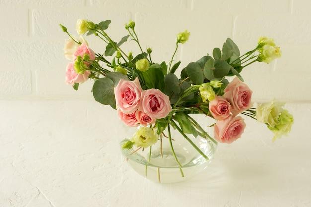Vase mit schönen rosen, eustoma und eukalyptusblumen auf dem tisch. zarte grußkarte für den urlaub.