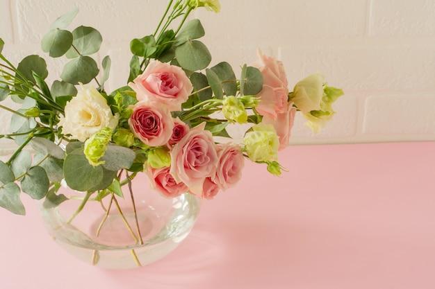 Vase mit schönen rosen, eustoma und eukalyptusblumen auf dem tisch.