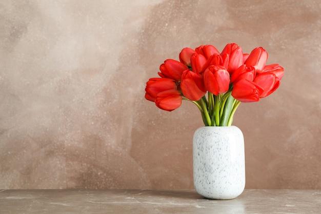 Vase mit schönen roten tulpen auf tisch gegen braun