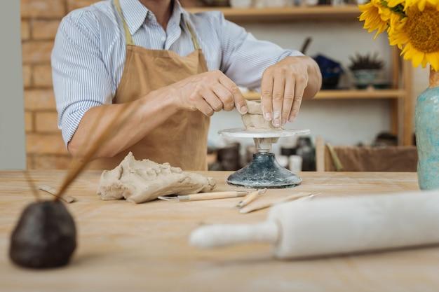 Vase mit sonnenblumen. kreativer professioneller keramiker, der keramikjigger verwendet, der nahe vase mit sonnenblumen steht