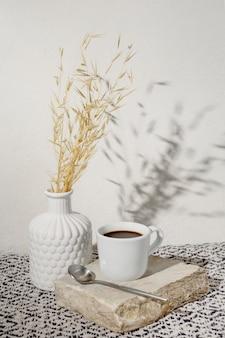 Vase mit trockenem weizen und einer tasse kaffee