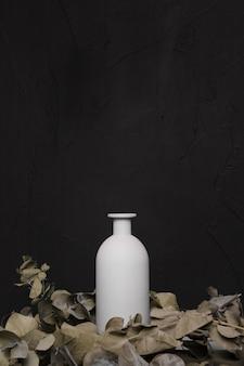 Vase mit trockenen blättern auf dunklem hintergrund