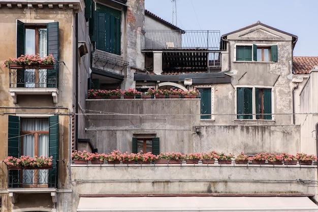 Vasen mit blumen in der mitte der bunten häuser des hofes in venedig, italien