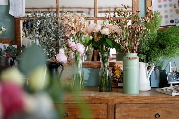 Vasen mit bunten exotischen blumen auf einer verkaufstheke