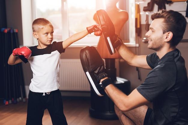 Vater-and son boxing-übungen, die in der turnhalle ausbilden.