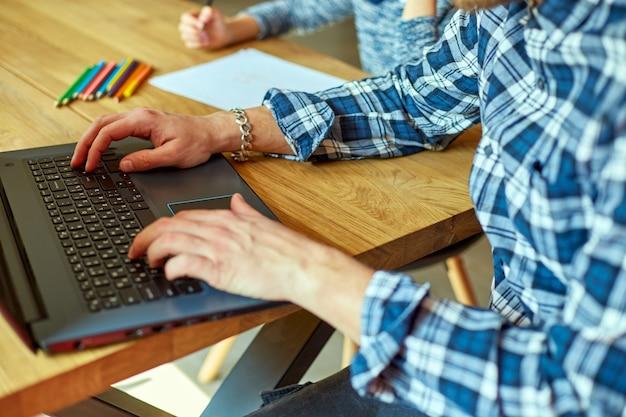 Vater arbeitet in seinem homeoffice an einem laptop, ihre tochter sitzt neben ihr und zeichnet