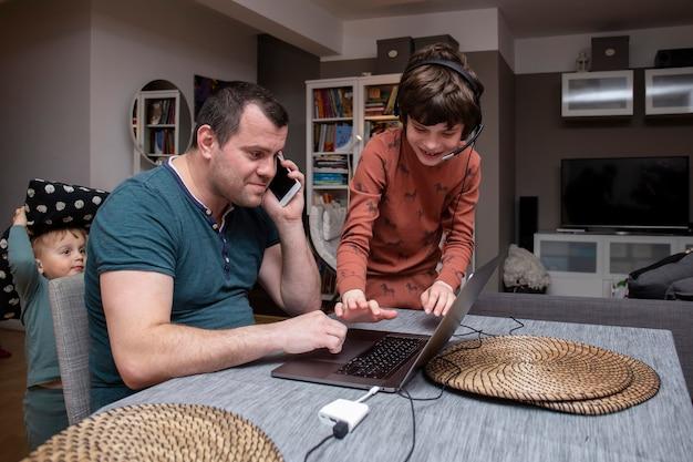 Vater arbeitet von zu hause aus mit kindern während des ausbruchs des coronavirus