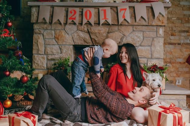 Vater auf dem boden liegend mit einem kamin im hintergrund, während sein baby aufrichten und die mutter schaut sie lächelnd