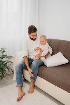 Vater auf der couch hält sein baby zu hause