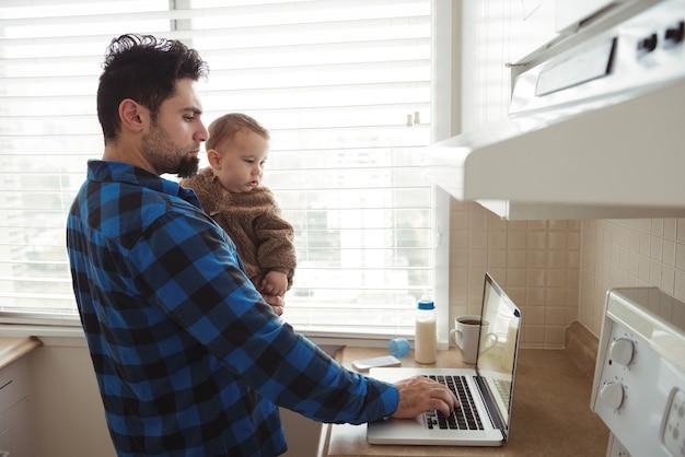 Vater benutzt laptop, während er sein baby in der küche hält