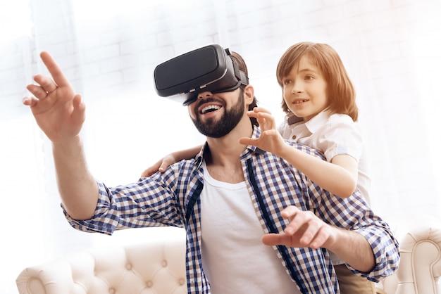 Vater benutzt virtuelle brille zusammen mit sohn zu hause.