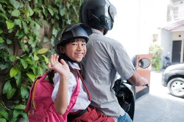 Vater bringt seine tochter morgens mit dem motorrad zur schule. asiatischer grundschüler in uniform, der zurück zur schule geht