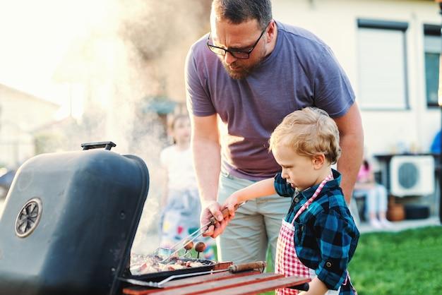 Vater bringt seinem kleinen sohn das grillen bei, während er im sommer im hinterhof steht. familientreffen-konzept.