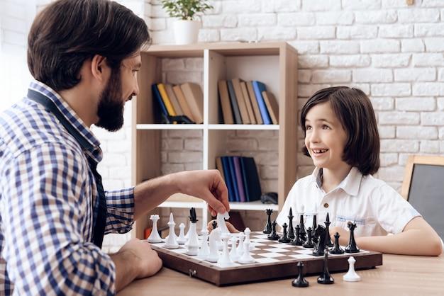 Vater bringt seinem kleinen sohn das schachspielen bei.