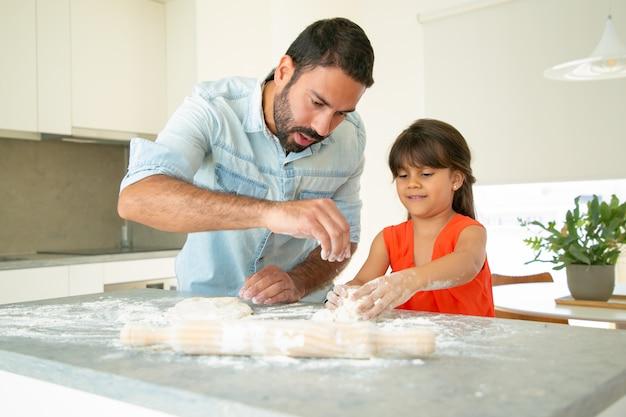 Vater bringt seinem mädchen bei, brot oder kuchen zu backen. konzentrierte vater und tochter kneten teig auf küchentisch mit mehl unordentlich. familienkochkonzept
