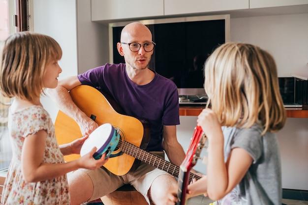 Vater bringt seinen töchtern bei, wie man gitarre spielt und instrumente spielt