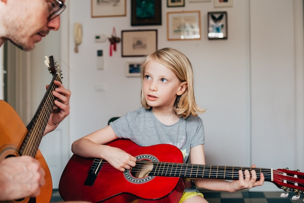 Vater bringt seiner tochter das gitarrenspielen bei