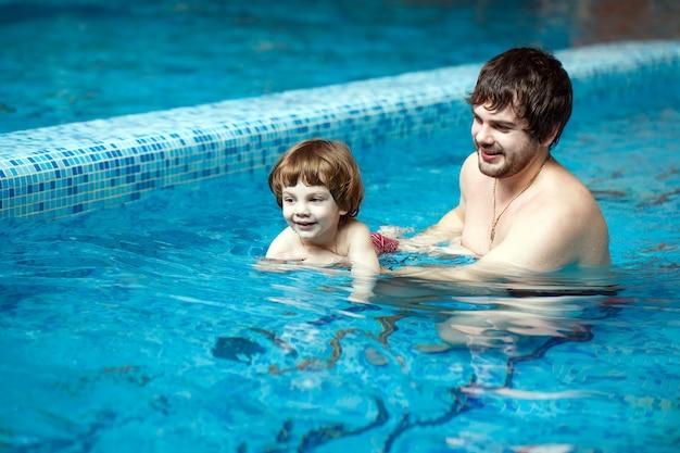 Vater bringt sohn bei, im pool zu schwimmen.