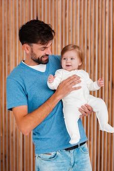 Vater, der baby mit hölzernem hintergrund hält